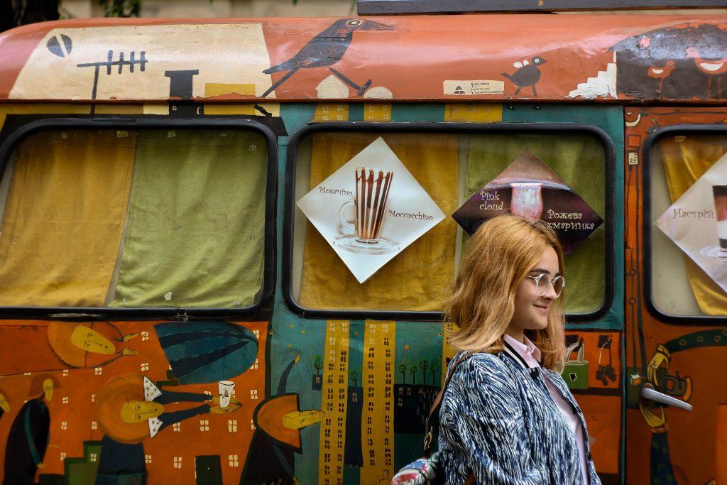 jeune femme rousse devant un van peint
